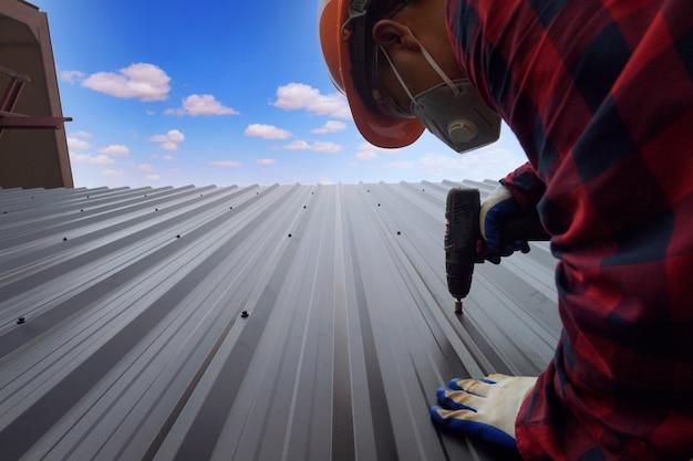 L'operaio edile del roofer installa un nuovo tetto, strumenti per tetti, trapano elettrico utilizzato su nuovi tetti con lamiera metallica.