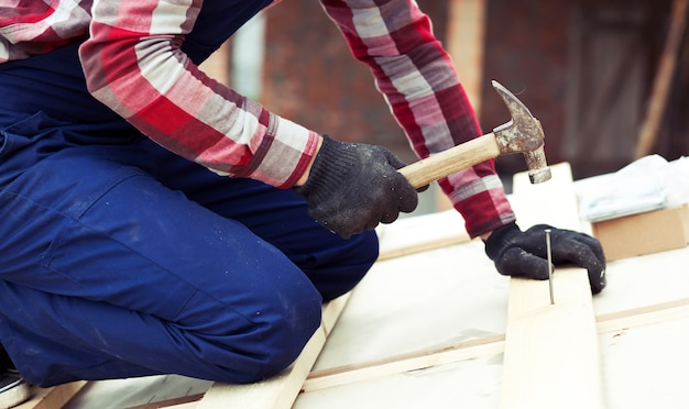 Lavoratore del roofer che martella il chiodo nella plancia di legno