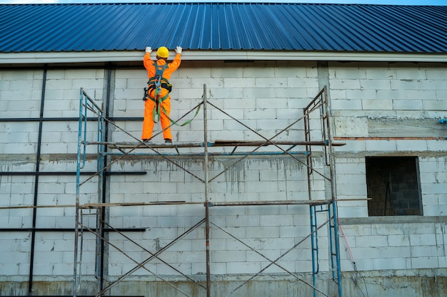 Operaio di roofer in usura uniforme protettiva e lavoro di linea di sicurezza installare un nuovo tetto in cantiere.