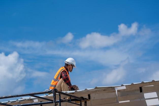 Copertura, operai edili che indossano il controllo delle cinture di sicurezza e montaggio dell'installazione di un nuovo tetto, strumenti di copertura.