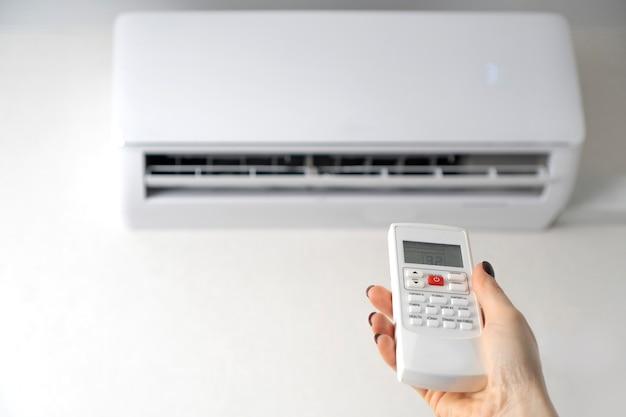 Aria condizionata in camera. telecomando del condizionatore d'aria in mani femminili