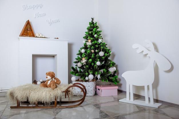 Camera decorata con decorazioni natalizie. albero di natale, camino, slitta e renne.