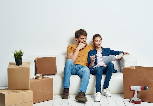 Una stanza su un divano bianco con scatole per traslocare appartamenti