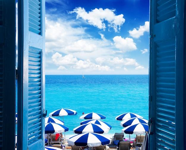 Camera con porta aperta al paesaggio marino estivo.