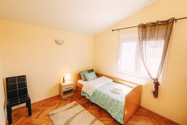 Una stanza con un soffitto inclinato e una finestra di plastica con un letto con una sponda una sedia e un comodino