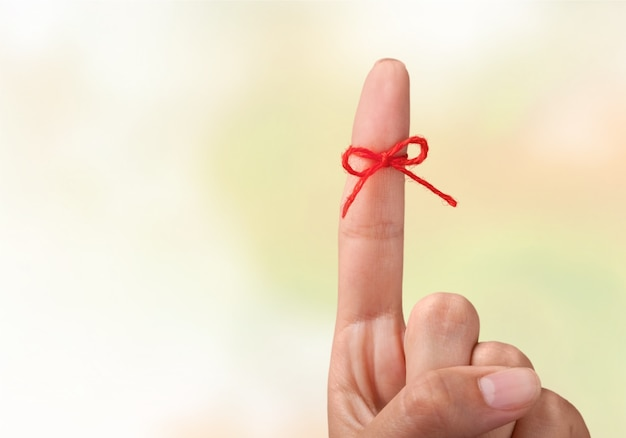 Fiocco di corda sul dito rivolto verso l'alto sullo sfondo