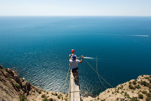 Salto con la corda da una scogliera con una corda nell'acqua. l'oceano. mare. montagna