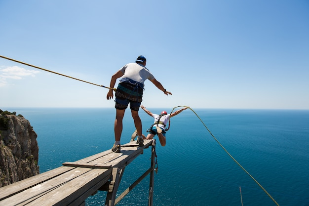 Corda che salta giù da una scogliera con una corda in acqua. l'oceano. mare. montagna.