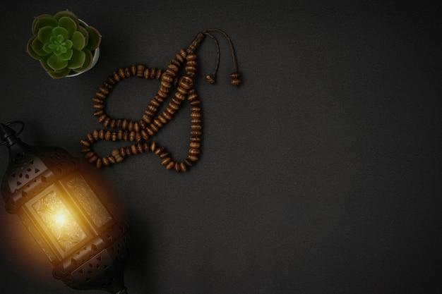 Grani del rosario e lanterna della candela sul nero
