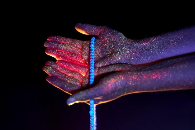 Rosario in mano, preghiera. luce attraverso i palmi delle tue mani in perline ultraviolette, dio e religione. luce divina attraverso le tue dita, profeta maometto