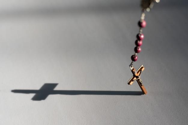 Il rosario appeso su una superficie liscia crea un'ombra trasversale
