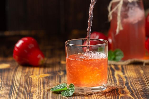 Succo di mela rosa su superficie di legno scuro