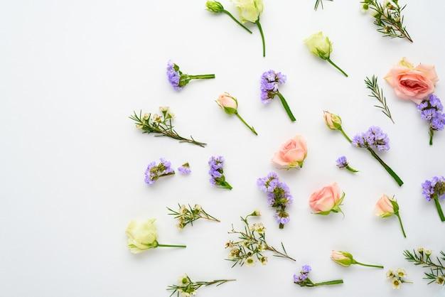 Boccioli di rosa, eustoma, infiorescenze di limonium su bianco