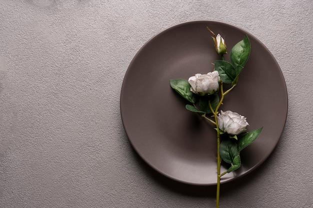 Rosa in un piatto marrone scuro, decorazioni e decorazioni, natura morta minimalista su uno sfondo grigio, copyspace.