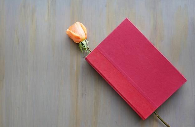 Fiore di rosa e libro dalla copertina rigida rosso su fondo di legno.