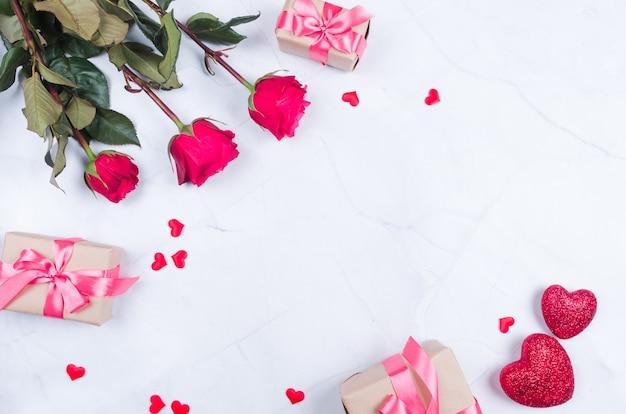 Rose fiori con regali sul tavolo dall'alto con copia spazio, piatto laici.