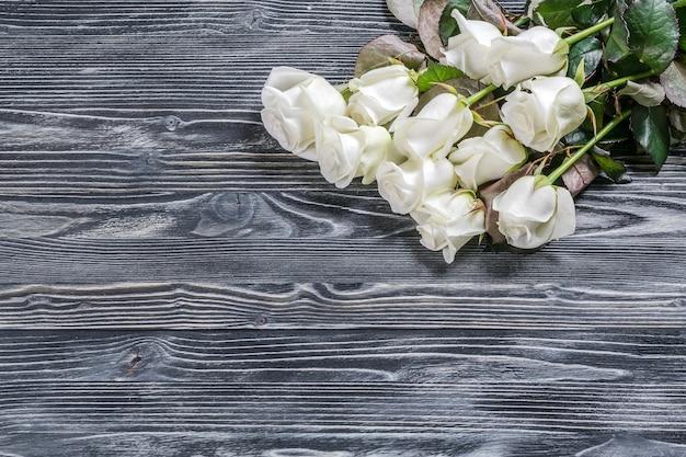 Fiori di rosa sulla superficie rustica in legno
