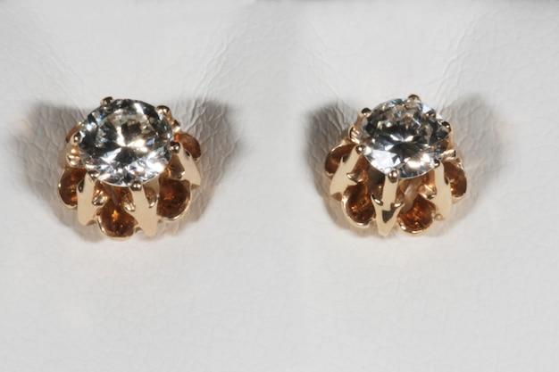 Orecchini solitari in oro rosa con diamanti su fondo bianco