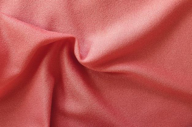 Priorità bassa di struttura del tessuto in oro rosa, motivo sgualcito di seta o lino.