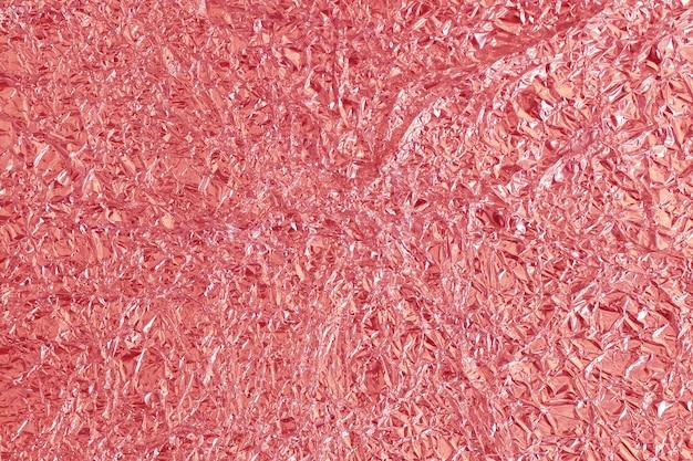 Struttura brillante della stagnola di oro rosa, carta da imballaggio rossa astratta per fondo e opera d'arte di progettazione.