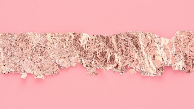 Striscia di carta oro rosa strappata su sfondo rosa, copia spazio, design artistico.