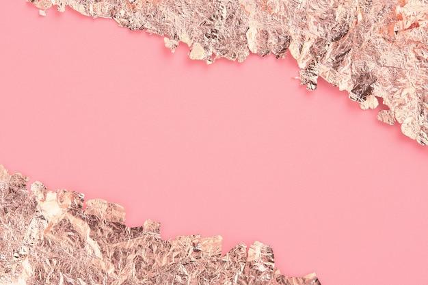 Cornice con bordi strappati in carta oro rosa, sfondo rosa pastello, copia spazio.