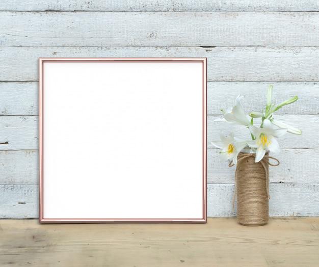 Mockup di cornice quadrata rose gold vicino a un mazzo di gigli si trova su un tavolo di legno su uno sfondo di legno bianco dipinto. stile rustico, bellezza semplice. 3 rendering.