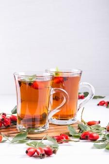Tè al cinorrodonte in tazza trasparente con miele e frutti di bosco freschi. bevanda della vitamina c sulla tavola bianca