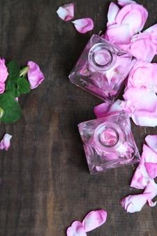 Olio di rose in bottiglie su spazio in legno di colore