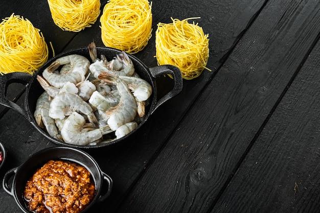 Set di ingredienti per pasta di gamberi al pesto di rose, su legno nero