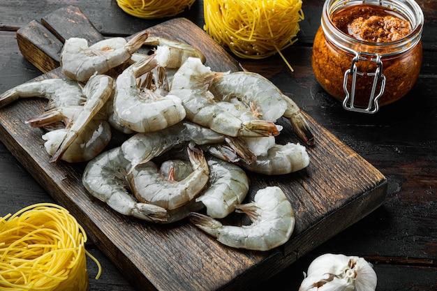 Set di ingredienti per pasta di gamberi al pesto di rose, su un vecchio tavolo di legno scuro