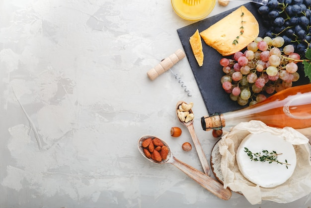 Noci di formaggio bottiglia di vino rosato e uva rosa e nera su tavola di ardesia e miele. camembert, snack da wine bar. composizione del vino su fondo di cemento rustico grigio chiaro con spazio di copia.