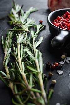 Le erbe del rosmarino si chiudono su sulla tavola di pietra nera con le spezie e la carne cruda vicino al fuoco selettivo di vista laterale verticale.