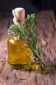 Rosmarino erbe ed erbe medicinali. mazzo di rosmarino fresco e olio su fondo in legno