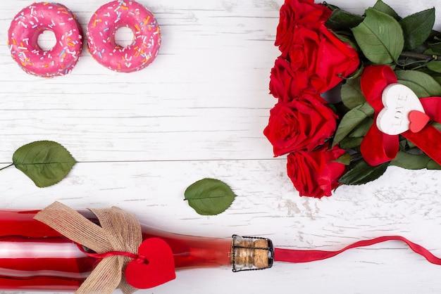 Rose, bottiglia di champagne, ciambelle, cuore decorativo, nastro rustico, sulla superficie in legno.