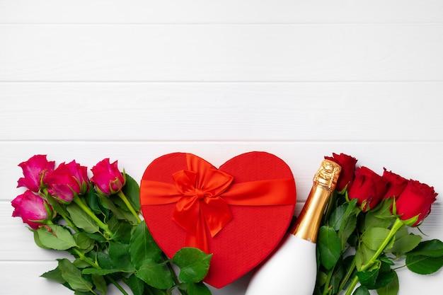 Bouquet di rose, bottiglia di champagne e confezione regalo vista dall'alto