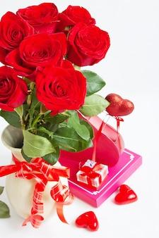 Bouquet di rose, scatole regalo e simbolo del cuore su bianco