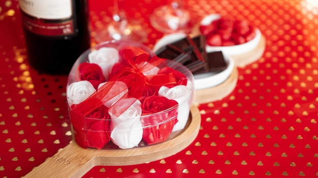 Rose, cioccolatini e dolci su piatti a forma di cuore. impostazione della tavola festiva per la data degli innamorati. sfondo rosso