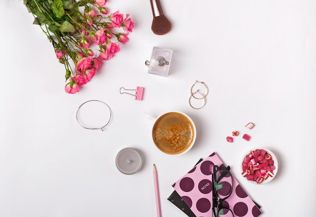 Rose, caffè e piccoli accessori femminili eleganti sullo sfondo bianco