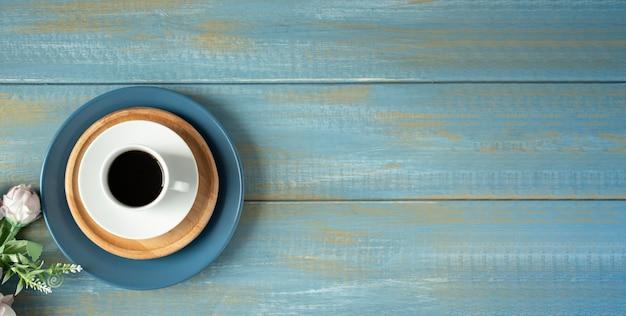Rose e tazza di caffè sulla tavola di legno. vista dall'alto con copia spazio