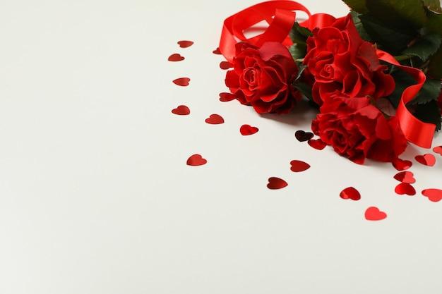 Rose, cuori decorativi e nastro su sfondo bianco