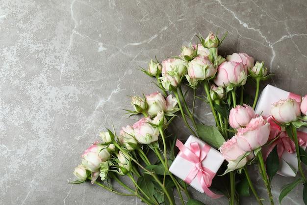 Rose e scatole regalo su sfondo grigio con texture