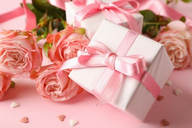Rose e scatole regalo su sfondo rosa, da vicino