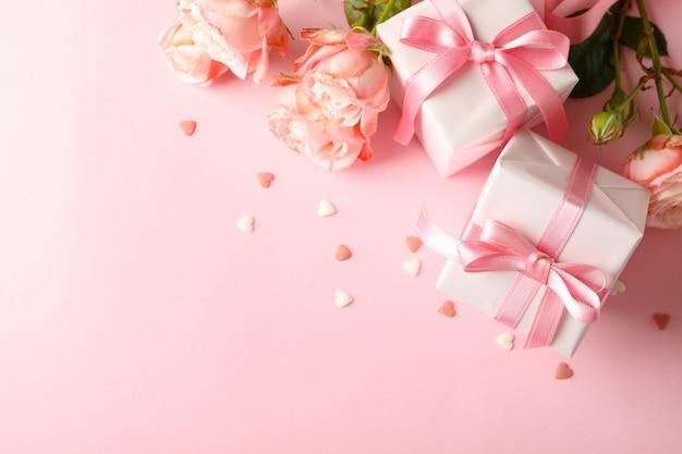Rose e scatole regalo su sfondo rosa, spazio per il testo