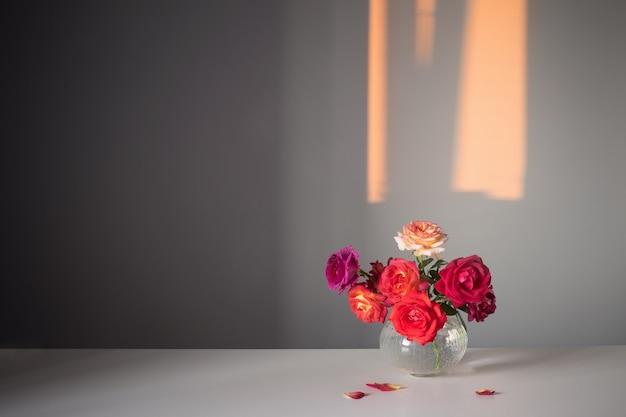 Rose in vaso di vetro su sfondo grigio