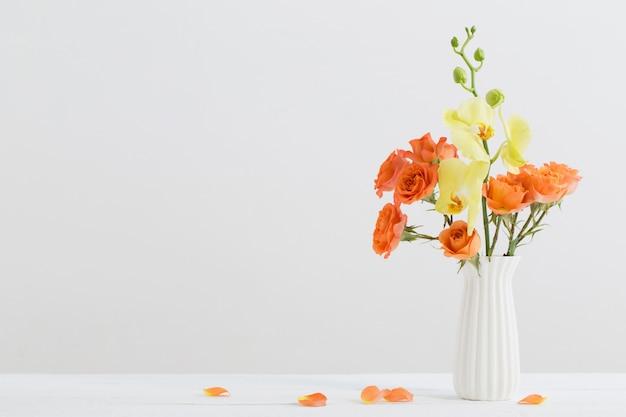 Rose e orchidee in vaso bianco