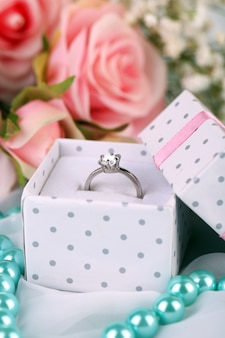 Rose e un anello su un panno bianco Foto Premium