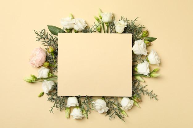Rose, rami di thuja e spazio per il testo su sfondo beige