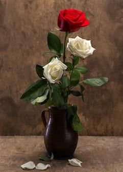 Rose in un vaso su uno sfondo di legno