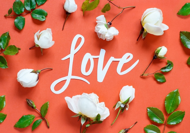 Rose e parola amore su uno sfondo rosso da vicino
